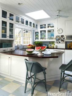 "Stained oak countertops ""ground the white in the kitchen,"" designer Lynn Morgan says of her Savannah row house."