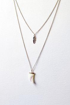 Colar Dente de Madrepérola. Colar com duas correntes, uma com pingente de dente confeccionado em madrepérola e outra com pena em metal prata.