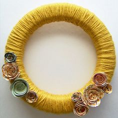 Embellish with Rosettes - Wrap yarn around a foam wreath for a homespun look, then embellish with paper flowers for a classic decor piece.