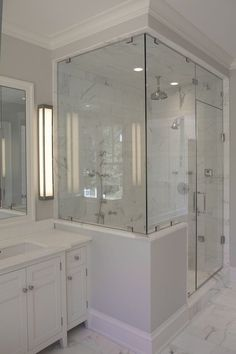 source: Jillian Klaff Homes    Master bathroom with cool gray paint color, seamless glass shower with marble tiles shower surround, polished nickel rain shower head, white bathroom vanity and marble tiles floor.