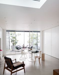 White Minimalist Dining Room with Sliding Doors to Courtyard