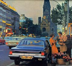 Diplomat visiting the Kurfürst 1970 calendar - Opel Diplomat V8  Chevy power and transmission - a car that was so excellent, but failed to warm the hearts of the ones who could afford it.  Something strange here. The guy is so eager to give his ladyfriend the flowers, that he grabs the hand of the flower lady with it. And his ladyfriend acts overly surprised, I have to say.  Location: Kurfürstendamm, Berlin.