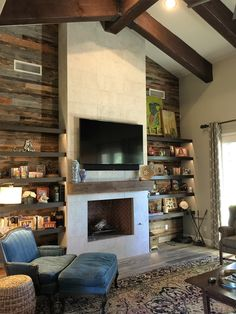 This 16' fireplace mixed contemporary limestone facing with reclaimed barnwood behind the open shelves and a reclaimed mantel from the 1880's to make a stunning and inviting area.