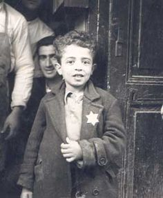 September 1, 1941: German government orders Jews to wear yellow stars. Anti-Jewish laws were also enforced in Italy, under the dictatorship of Mussolini. This photograph pictures a young Jewish child with a Star of David badge from Rhodes, where Anti-Jewish laws were in effect.