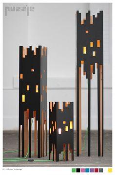 """Lightheat è la linea di lampade proposta da Puzz'le. Tre """"grattaceli"""" in legno di faggio, illuminati come la facciata di un palazzo con tante finestre. Un progetto semplice, basato sulla capacità di montaggio e sul risparmio di materiale."""
