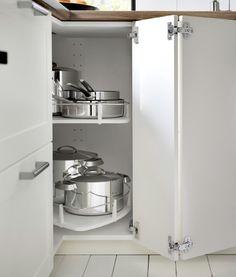 METOD Eckunterschrank mit Karussell in Weiß mit GRYTNÄS Front in Elfenbeinweiß; die geöffnete Tür zeigt das mit Kochgeschirr befüllte Karussell.