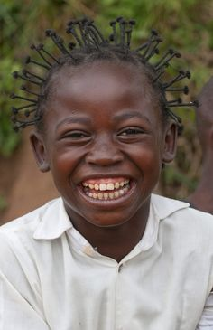 A young girl greets visitors in Kamina, Democratic Republic of Congo.