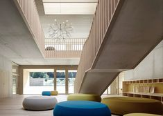 Huge round cushions in shades of mustard yellow and cornflower blue add colour to the pale concrete and timber interior of this kindergarten in western Austria