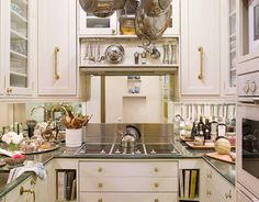 """This tiny New York City kitchen has a place for everything, says designer Stephanie Stokes. """"After designing so many kitchens for other people, I knew exactly what I needed and what I wanted,"""" she says. A mirrored backsplash, an electric cooktop that doubles as countertop, and simple cabinetry help give the illusion of grandeur."""