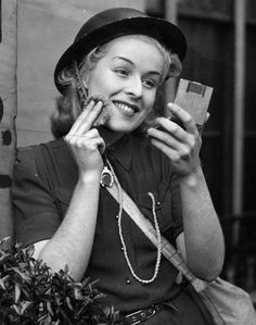 30th September 1939: Air raid warden Judy McCrea puts on some make-up while on duty at Paddington. She is a showgirl at the Windmill Theatre in London. (Photo by William Vanderson/Fox Photos/Getty Images)