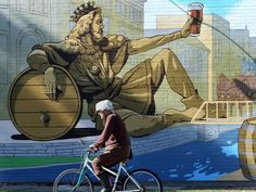 "Check out Cincinnati's new murals. Photo: A bicyclist pedals past King Gambrinus, an icon of beer, whose image is included in the mural ""Cheers to Cincy, Past and Present."" on the wall of the Samuel Adams Brewery in the 1600 block of Central Parkway.  The Enquirer/Patrick Reddy"