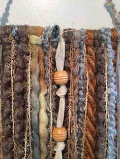 This gorgeous small yarn wall hanging is made with many different texture yarns, beads, fabric and mounted on a piece of driftwood. The colors are grey, cream, pale blue, rust and grey It measures 14.5 wide and 30 long. The measurement includes the hanger and the width of the