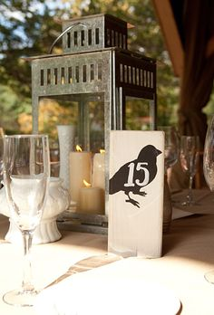 The centerpieces were comprised of rustic lanterns filled with candles, and table numbers featured a bird motif. Lorraine Daley Wedding Photography and Allure West Studios.