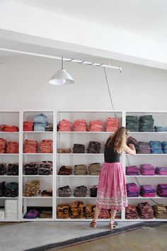 Stacks of folded fabric on white shelves organized by color in the artist studio space of Block Shop Textiles.