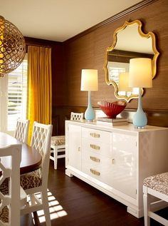 Glossy white lacquer buffet, turquoise blue lamps, gold mirror, gold drapes, white dining chairs, brown grasscloth wallpaper and chandelier.