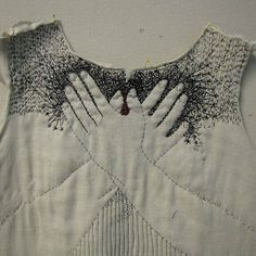 Embroidered hands on chest.  Beautiful black and white stitches.