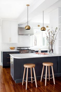 All-white kitchen with gold pendant lights
