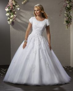 A fairytale ball gown fit for a princess. The sequin lace bodice sparkles with a slimming ruched waist. The lace continues to fall delicately down the full gathered skirt and train.   Bonny Bliss Bridal: Style 2409   Modest Wedding Gown
