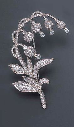 A DIAMOND LILY OF THE VALLEY BROOCH Designed as a pavé-set diamond lily of the valley stem extending similarly-set undulating leaves and articulated flowers each with a circular-cut diamond accent and suspending a diamond briolette mounted in 18k white gold (one briolette-cut diamond deficient)