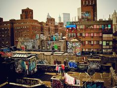 Chinatown Rooftop Graffiti - New York City - By Vivienne Gucwa  New York City is an urban layer cake.   This is another one of my favorite views in lower Manhattan. It's a small segment of an entire universe that exists above millions of New Yorkers.   Layers of colorful graffiti cover the rooftops of these Chinatown apartment buildings as rooftop doors blow open in the wind and colorful clothing sways on clotheslines high above the city below.  ---
