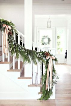 новогодний декор лестницы с хвоей и атласными лентами