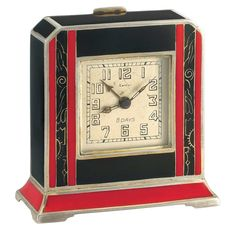 Art Deco Silver and Red and Black Enamel 8 Day Desk Clock, Cartier  Mechanical, the cut-cornered rectangular case applied with black enamel, centering a square-shaped silver-tone dial with Arabic numerals, flanked by four red enamel bands spaced black enamel with gold decoration, atop a red enamel base, with gilt case and interior, case and movement signed Continental Lemania Inc. Swiss, with hallmark, circa 1920. 3 1/16 x 3 1/16 x 1 3/8 inches.