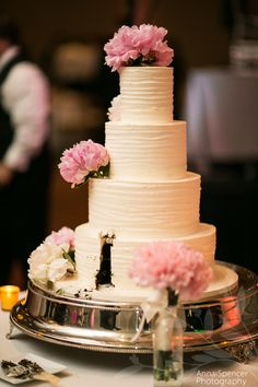 Chocolate wedding cake with simple white icing and pink peonies.