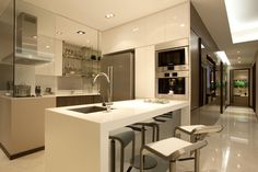 KITCHEN: Shiny white cabinets, white floor, white walls, steel appliances, bar stools, glass wall