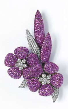 A Pink Sapphire and Diamond Flower Brooch Designed as two articulated pavé-set pink sapphire flowers, centering upon circular-cut diamond florets, extending pavé-set pink sapphire and diamond leaves, mounted in oxidized 18K white gold, length 3 inches.