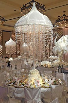 Instead of chandeliers, this designer used white satin canopies over each guest table, crystals and small white flowers hang down from the canopy creating a floating centerpiece!