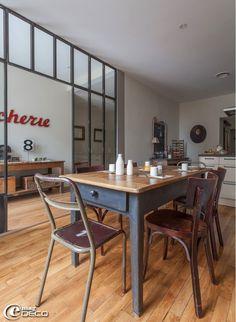 Dans une cuisine, deux chaises industrielles en bois et métal chinées chez Nicole Guiheneuc