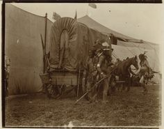 Indian performers, backstage at Buffalo Bill's Wild West Show. Three unknown performers, wearing war paint and breech cloths, wait behind tall fabric screens for their moment in front of the audience. Horses and a covered wagon can be seen in the background, as well as the top of a large tent. From The Chris Kortlander Collection 2007 Dallas, TX - Harrisburg Western Photography & Artifacts Signature Auction #679