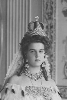 Her Imperial and Royal Highness Princess Wilhelm of Sweden, née Her Imperial Highness Grand Duchess Marie Pavlovna of Russia. She is wearing two different pieces. In front is the tiara that all Romanov brides wore at their weddings. Behind it is a small crown, also worn by all Imperial brides. Her earrings are also part of the traditional wedding finery and the huge diamonds were so heavy they caused pain after a few hours.