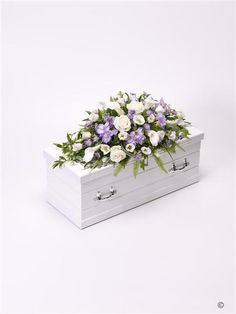 Children's Casket Spray - Blue and Lilac. This delicate casket spray arrangement includes pure white calla Lily and large-headed roses contrasted with sweetly fragrant lilac freesia, September flowers and purple lisianthus. The display is trimmed with China grass, ruscus, asparagus fern and ivy trails