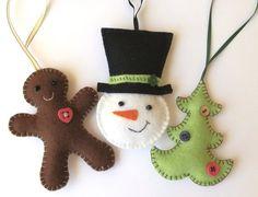 Añadir un toque lindo a tu árbol de Navidad este año, con este conjunto de tres hecho a mano fieltro adornos: un muñeco de nieve, un hombre de pan de jengibre y un árbol de Navidad.  Muy spiffy en su sombrero, el muñeco de nieve es 10cm desde la barbilla a la parte superior de su sombrero, con un lazo de cinta de 12cm para colgar. El hombre de jengibre es también 10cm de altura, con un lazo de cinta de 9cm. El árbol de Navidad es 9cm de altura, con un lazo de cinta de 10.5cm.  Cada ornamento…