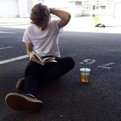 Thomas Brodie-Sangster just be reading on the ground in the parking lot with…