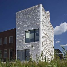 Strips of perforated fabric are tacked onto the facades of this house near Amsterdam