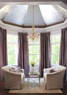 This would be a lovely sitting room off of the master bedroom.  I would choose other colors, but I like the architecture of the room.  Dome ceiling, bay windows covered in plum silk sinch-pleat curtains, white tufted settees, purple pillows and Global Views French Square Leg Cocktail Table.  Traditional Home - Hampton Designer Showhouse