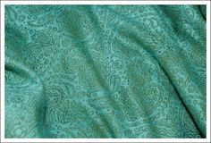 """A new luxurious wrap from Ellevill in 50 % linen and 50 % bamboo. Two colored ingreen and bluePaisley pattern is a droplet-shaped vegetable motif of Indian and Persian origin, similar to half of the Yin yang symbol. The pattern is sometimes called """"Persian pickles"""" by American traditionalists, especially quiltmakersas far back as 1888.In Sanskrit the design is known as mankolam and has long been used in India. It resembles a mango and has sometimes been associated with Hinduism.Some design…"""