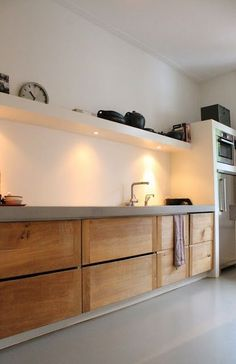 Skattejakt: House for Sale Warm wood tones against gray and white. Large drawers vs. cabinets. No uppers, only shelving with downlighting for tasks.