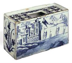 A BRISTOL DELFT BLUE AND WHITE RECTANGULAR 'BRICK' CIRCA 1740 Both long sides painted with a maritime scene of fortified buildings on a shore with sails in the distance, the side panels with stylized flowers, the top pierced with a large rectangular aperture flanked by two rows of small circular apertures, painted with diaper and scrolls 6 1/8 in. (15.5 cm.) wide