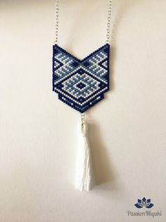 Collier Modèle ETZALLI avec perles Miyuki delicas 11/0 ... 100% fait main , modèle inventé et tissé entièrement à la main ! Composition : - Perles : Bleu nuit , Bleu pâle et Blanc - Apprêts : Métal Argenté - Pompon : Fil de broderie blanc Taille : - Longueur Totale : 370 mm -