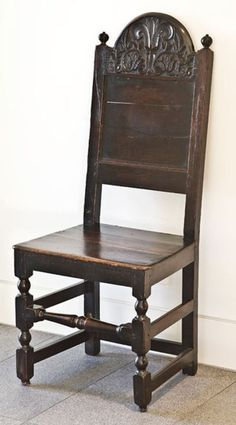 A 17th Century English oak decorative occasional chair, having a dome shaped top rail, flanked by turned finials, above an inverted panel. Having a wooden seat, resting on turned and block legs, joined by stretchers.    C. 1680