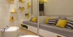 Neste ambiente, as arquitetas Daniella e Priscilla de Barros criaram uma estante com nichos desencontrados e formatos diferentes. A cama em marcenaria acompanha a bancada com TV. A utilização do amarelo, cinza e preto no mobiliário e objetos de decoração, traz um aspecto lúdico ao ambiente.