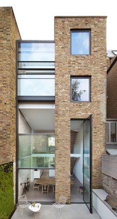 Studio Octopi has overhauleda terraced house in north London, adding an extension that featuresa three-storey-high windowand pivoting door.