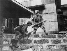 During the hard street fighting against Japanese strongpoints at the New Police Station, Pandacan district, GIs of the 129th Infantry Regiment, 37th Infantry Division, climb through some Japanese barbed wire in Manila, Philippines. 13 February 1945.