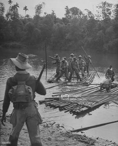French soldiers fighting against Viet Minh improvising rafts for forging streams during patrol of delta.