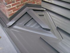 Standing seam painted steel roof - view of chimnet saddle and counter flashing.