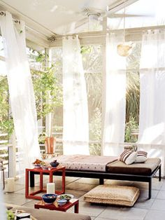 Gauzy curtain panels, daybeds, and woven floor cushions give this South Carolina porch the feel of an exotic resort.