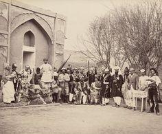 Grupo teatral, Kandahar-Los miembros del grupo están disfrazados con diferentes trajes cómicos. Un hombre, en el extremo izquierdo del retrato, está disfrazado de madre que sostiene a un «niño» muy poco sano. Otros soldados están disfrazados como miembros de las tribus afganas, sijes, mendigos, bufones y un vendedor de «pasteles calientes de camello».